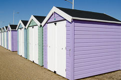 Pastel coloured beach huts. A row of pastel coloured beach huts overlooking the sands at Weston-Super-Mare. Viewed from pavement on a sunny day in August royalty free stock photos