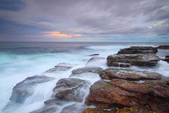 Pastel colours of sunrise. The tranquil flow of water over a coastal shoreline stock images