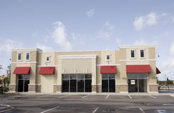 Pastel commercial store red awning. Upscale pastel strip mall building with red awnings and tinted glass Royalty Free Stock Photos