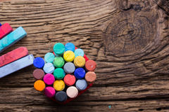 Pastel crayons and pigment dust on old wooden background. Royalty Free Stock Photography