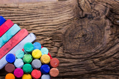 Pastel crayons and pigment dust on old wooden background. Stock Image
