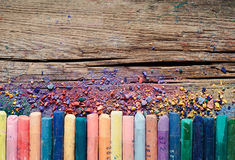 Pastel crayons and pigment dust on rustic wooden background. Royalty Free Stock Photos