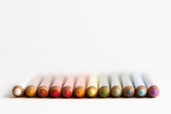 Pastel crayons in a row Royalty Free Stock Photos