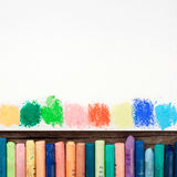 Pastel crayons and white paper sheet of sketchbook with spots of Royalty Free Stock Image
