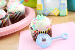 Pastel Cupcakes. One cupcake with white icing and pastel sprinkles with a baby rattle. Concept is for a baby shower and a child's birthday party stock images