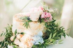 Pastel de bodas adornado con las flores frescas Imagen de archivo libre de regalías