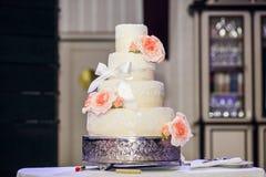 Pastel de bodas adornado con las rosas, el cordón y el arco Fotos de archivo