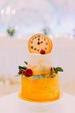 Pastel de bodas adornado con los relojes y las flores cerca para arriba Foto de archivo