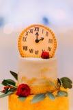 Pastel de bodas adornado con los relojes y las flores cerca para arriba Imagen de archivo