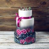 Pastel de bodas adornado en rosas azules y púrpuras rústicas del estilo Imagen de archivo libre de regalías