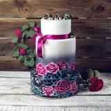 Pastel de bodas adornado en rosas azules y púrpuras rústicas del estilo Imagen de archivo