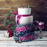Pastel de bodas adornado en rosas azules y púrpuras rústicas del estilo Foto de archivo