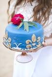 Pastel de bodas azul en las manos de la novia Fotografía de archivo libre de regalías