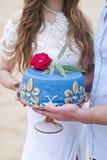 Pastel de bodas azul en las manos de la novia Imagenes de archivo