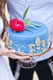 Pastel de bodas azul en las manos de la novia Fotos de archivo libres de regalías