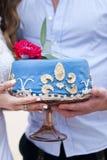Pastel de bodas azul en las manos de la novia Fotografía de archivo