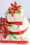 Pastel de bodas blanco adornado con las decoraciones y las flores rojas del azúcar - lilys Imágenes de archivo libres de regalías