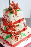 Pastel de bodas blanco adornado con las decoraciones y las flores rojas del azúcar - lilys Fotos de archivo libres de regalías