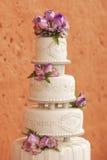 Pastel de bodas blanco adornado con las flores Imágenes de archivo libres de regalías