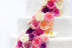 Pastel de bodas blanco adornado con las flores del azúcar imagenes de archivo