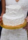 Pastel de bodas blanco en las manos de la novia Foto de archivo