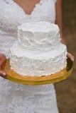 Pastel de bodas blanco en las manos de la novia Fotos de archivo libres de regalías
