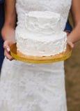 Pastel de bodas blanco en las manos de la novia Imagen de archivo