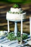 Pastel de bodas blanco hermoso con las flores al aire libre Imagen de archivo