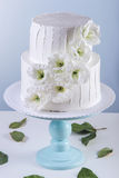 Pastel de bodas blanco de la litera adornado con las flores Imagen de archivo