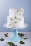 Pastel de bodas blanco de la litera adornado con las flores Fotografía de archivo