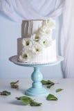 Pastel de bodas blanco de la litera adornado con las flores Foto de archivo libre de regalías
