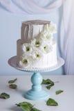 Pastel de bodas blanco de la litera adornado con las flores Imágenes de archivo libres de regalías