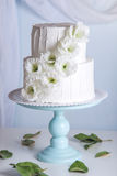 Pastel de bodas blanco de la litera adornado con las flores Fotos de archivo