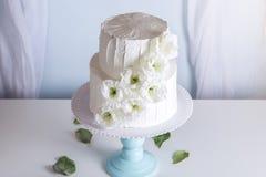 Pastel de bodas blanco de la litera adornado con las flores Imagen de archivo libre de regalías