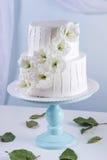 Pastel de bodas blanco de la litera adornado con las flores Foto de archivo