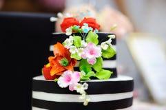 Pastel de bodas blanco y negro adornado con las flores del azúcar Foto de archivo libre de regalías