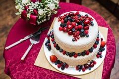Pastel de bodas clásico con las frambuesas, las fresas, las zarzamoras y el blueberrie foto de archivo
