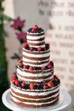 Pastel de bodas con gradas multi redondo con la esponja, la crema, el atasco y bayas en una base circular Arándanos frescos y Fotografía de archivo