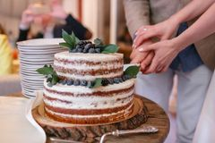 Pastel de bodas con las bayas en la tabla de madera La novia y el novio cortaron la torta dulce en banquete en restaurante imagenes de archivo