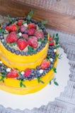 Pastel de bodas de dos niveles con los arándanos y las fresas con el euc Imágenes de archivo libres de regalías