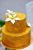 Pastel de bodas del oro adornado con las flores del azúcar blanco Fotos de archivo