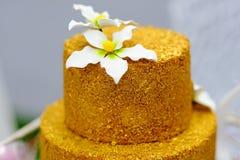 Pastel de bodas del oro adornado con las flores del azúcar blanco Foto de archivo