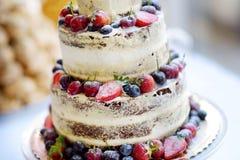 Pastel de bodas delicioso del chocolate adornado con las frutas y las bayas Imagenes de archivo