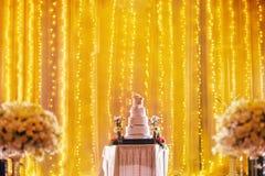 Pastel de bodas hermoso en la decoración de la etapa con la luz ámbar en el contexto Fotos de archivo libres de regalías