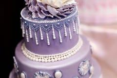 Pastel de bodas púrpura adornado con las flores Foto de archivo libre de regalías