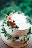 Pastel de bodas rústico adornado con los higos y el romero del verdor foto de archivo libre de regalías