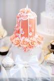 Pastel de bodas rosado adornado con las flores del azúcar Fotografía de archivo