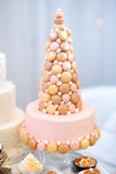 Pastel de bodas rosado adornado con los macarrones Fotos de archivo libres de regalías