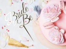 Pastel de bodas rosado con las rosas y los macarrones con la novia del primero a ser Visión superior, endecha plana Fotografía de archivo libre de regalías