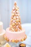 Pastel de bodas rosado delicioso adornado con los macarrones Foto de archivo